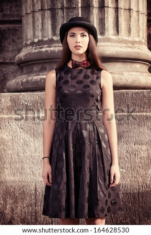 Beautiful brunette standing on the street of the old town. Retro style. - stock photo