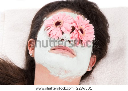 beautiful brunette taking a clay mask with her eyes covered in gerbera flowers - stock photo
