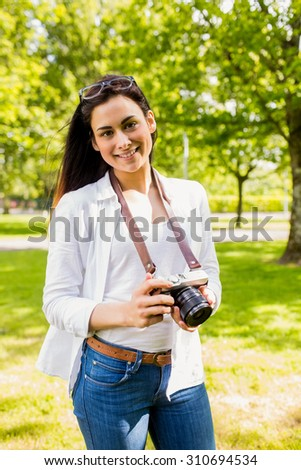 Beautiful brunette taking photo in the park on a sunny day