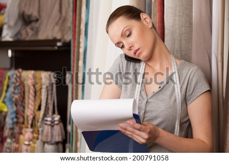beautiful brunette talking on phone and writing. attractive woman standing in drapery store - stock photo