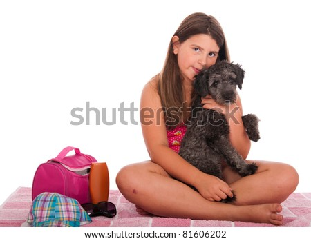beautiful brunette teenage girl in swimsuit at the beach with her shipoo dog (studio setting with beach and personal items) isolated on white background - stock photo