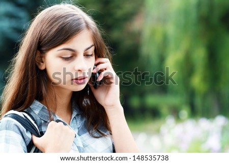Beautiful brunette teenage school girl calling on the phone outdoor in the park looking sad - stock photo