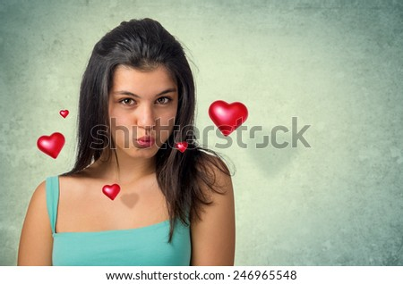 Beautiful brunette teenager expressing a kiss with hovering hearts - stock photo