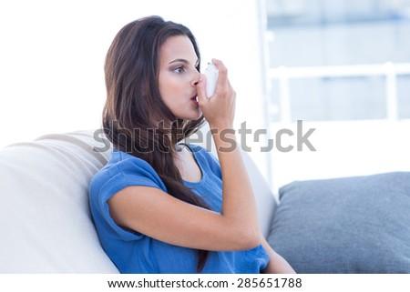 Beautiful brunette using inhaler in the living room - stock photo