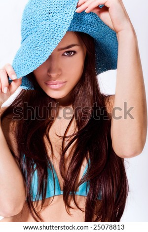 beautiful brunette wearing blue summer hat and bikini
