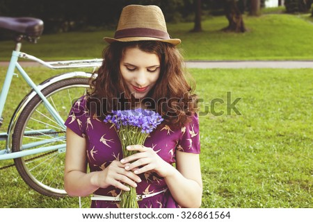 Beautiful brunette with a bouquet of cornflowers. Girl with retro bicycle. Girl in a park on the lawn. Beautiful girl with curly hair. Young girl in  purple dress and hat. Inhale the scent of flowers. - stock photo