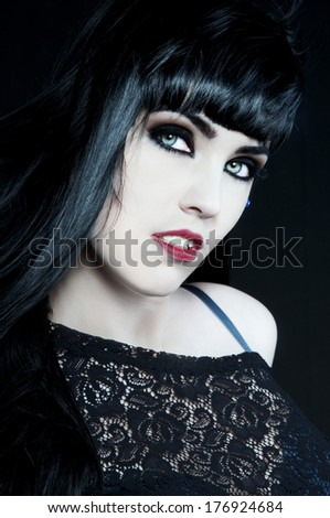 beautiful brunette with dark gothic makeup, white skin and red lips looking like a vampire - stock photo