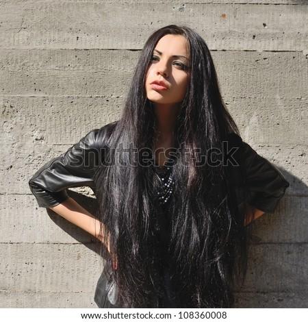 Beautiful Brunette Long Hair Against Concrete Stock Photo