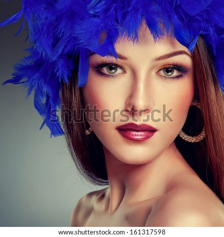 Beautiful brunette with long hair  in blue feathers - stock photo