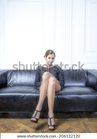beautiful brunette with long legs sitting on the couch - stock photo