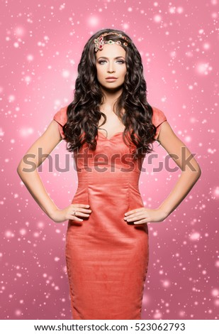 Beautiful brunette with luxury golden necklace over pink winter background. Christmas concept.