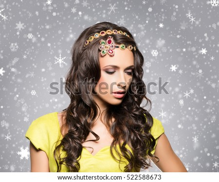Beautiful brunette with luxury golden necklace over winter background. Christmas concept.