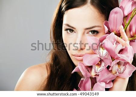 beautiful brunette with orchid portrait, studio shot - stock photo