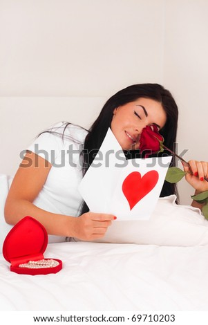 beautiful brunette woman at home was a gift from a loved one, postcard, heart and roses. feast day of St. Valentine - stock photo