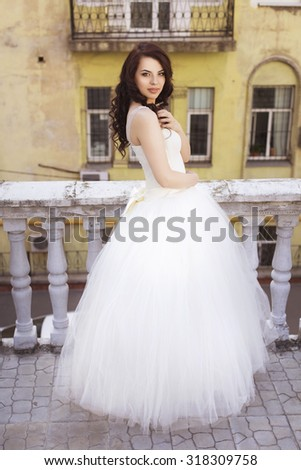 Beautiful brunette woman bride in a garden park in white wedding dress, curly hairstyle and a smile. warm weather, outdoors
