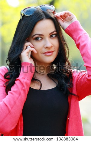 Beautiful brunette woman calling on the phone outdoor in the park - stock photo
