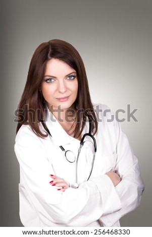 Beautiful brunette woman doctor, smiling cheerful female medical professional with arms crossed - stock photo