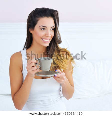Beautiful brunette woman drinking and enjoying morning coffee in bed