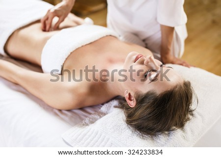 Beautiful brunette woman enjoys massage of tummy at the health spa - stock photo