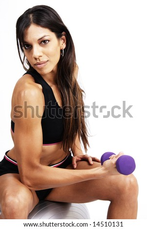 Beautiful brunette woman exercising with purple dumbbells sitting on a grey yoga ball - stock photo