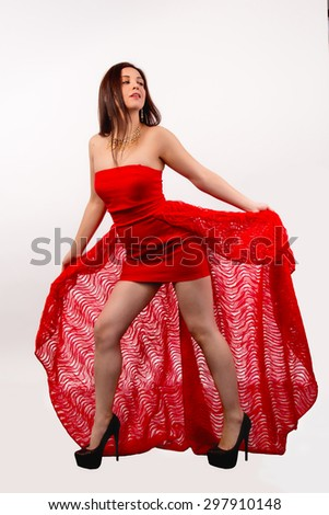 Beautiful brunette woman in a red dress isolated on white background
