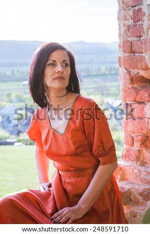 Beautiful, brunette woman in an old, abandoned house, wearing an orange dress, looking sad and melancholic. Photo has grain texture visible on its maximum size. Artistic photography  - stock photo