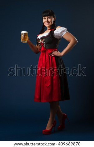 Beautiful brunette woman in Bavarian dressed with glass of beer - stock photo
