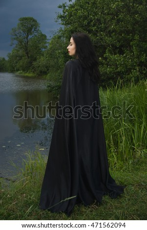 Beautiful brunette woman in black dress and black cloak. Gothic style.