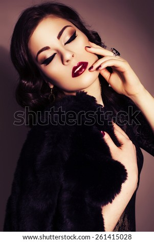 Beautiful brunette woman in black dress and fur coat with evening make up and waves retro  hairstyle. fashion posing - stock photo