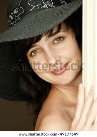 Beautiful brunette woman in black hat with naked shoulder looking fro behind a curtain