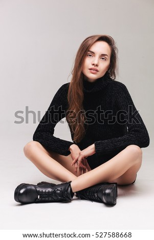 beautiful brunette woman in black jersey and black boots sitting on the floor. fashion studio shoot