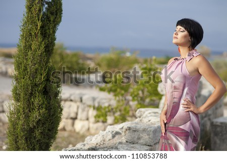beautiful brunette woman in bright dress in autumn park at Ancient wall of ruined city Hersones-Crimea.attractive slim sexy brown hair girl outdoor. Alluring lady with short hairstyle and makeup.