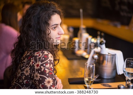 Beautiful brunette woman in evening dress sitting near bar counter. Blurred background.