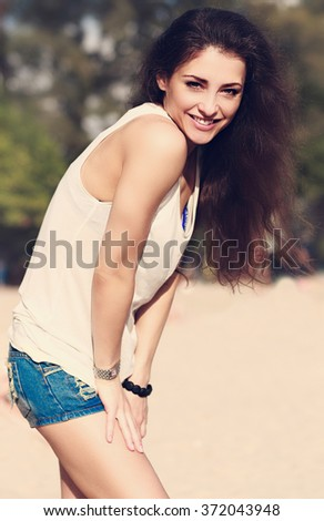 Beautiful brunette woman in fashion shorts and white top posing outdoors beach background - stock photo