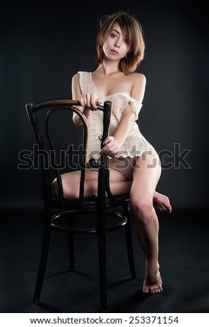 beautiful brunette woman in fishnet top and lingerie sitting on chair - stock photo