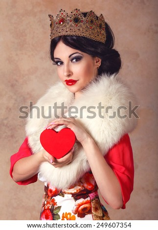 Beautiful brunette woman in golden queen crown and white fur collar holding a heart in her arms - stock photo