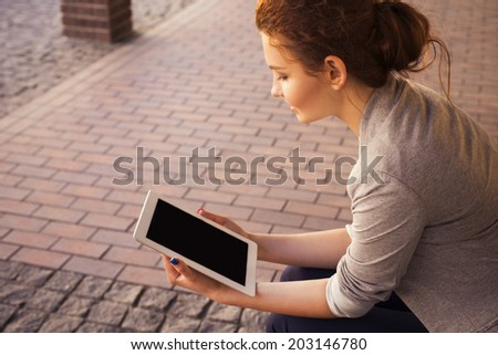 Beautiful brunette woman in grey jacket, dark trousers and white blouse with tablet outdoors. Copy Space - stock photo