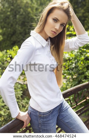 Beautiful brunette woman in neutral casual outfit walking in park. Lifestyle portrait. Summer day.
