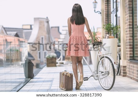 beautiful brunette woman in pink dress with bicycle and suitcase - stock photo