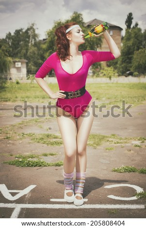 Beautiful brunette woman in pink retro body outfit with ponytail hairstyle and soda bottle in her hand. Outdoors - stock photo