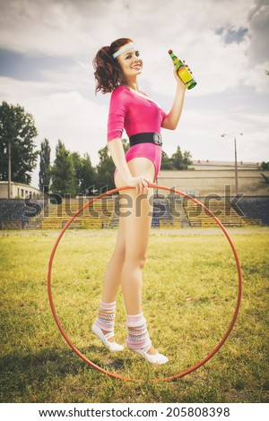 Beautiful brunette woman in pink retro body outfit with ponytail hairstyle, hula hoop and soda bottle in her hand. Outdoors - stock photo
