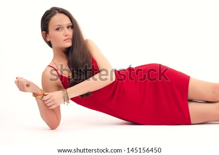 Beautiful brunette woman in red dress posing fashion in studio,woman lying down - stock photo