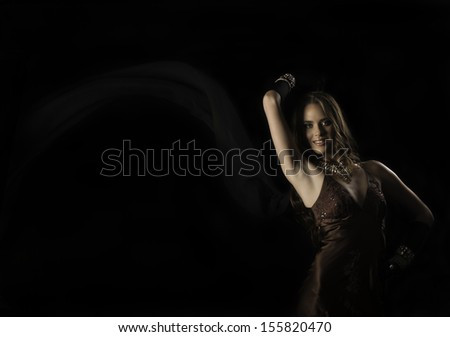 Beautiful brunette woman in vintage evening dress and long gloves, holding up a chiffon scarf blowing in the breeze against a black background