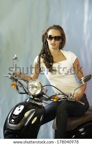 Beautiful brunette woman in white T-shirt and jeans, sitting on motor scooter and wearing sunglasses - stock photo