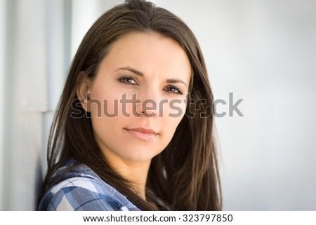 Beautiful brunette woman leaning on wall - stock photo