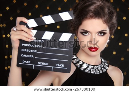 Beautiful brunette woman model holding film clap board cinema. Fashion portrait of girl with makeup, hairstyle and expensive jewelry.