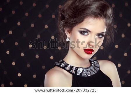 Beautiful brunette woman model with makeup and hairstyle in fashion earrings over bokeh lights background