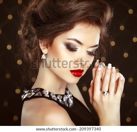Beautiful brunette woman model with makeup and hairstyle in fashion earrings over bokeh lights background - stock photo