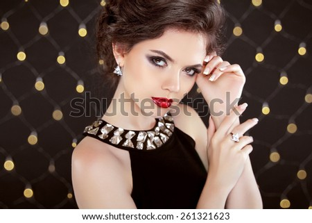 Beautiful brunette woman model with makeup and hairstyle in fashion jewels over bokeh lights background. Elegant lady.