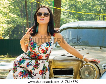 Beautiful Brunette woman near vintage car
